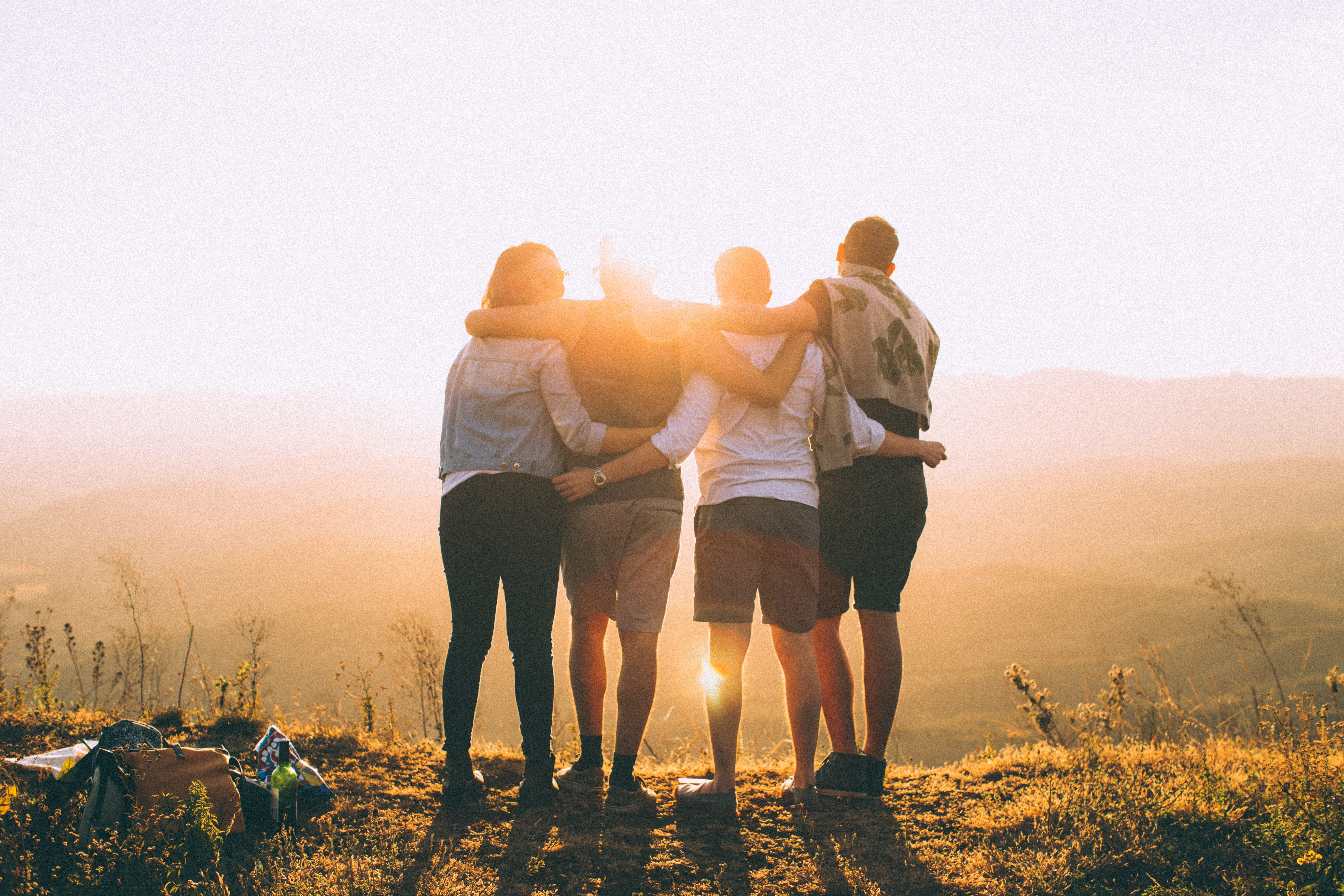 Four people hug after completing a hike.